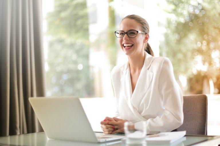 Lachende Frau mit Laptop im Büro beim Bewerber-Coaching