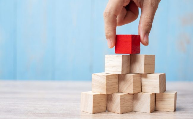 Businessman hand placing or pulling Red wooden block on the building. Business planning, Risk Management, Solution, strategy, different and Unique Concepts