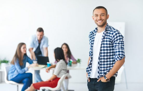 Successful businessman in front of diverse business team in modern office
